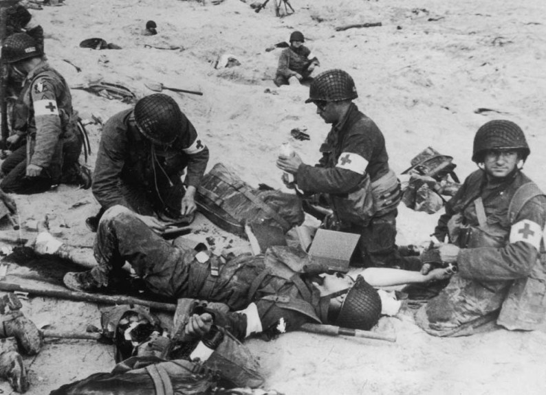 6th June 1944:  American medics administer first aid to wounded soldiers on Utah beach in Normandy, France, whilst in the background other troops 'dig-in' in the soft sand.  (Photo by Hulton Archive/Getty Images)