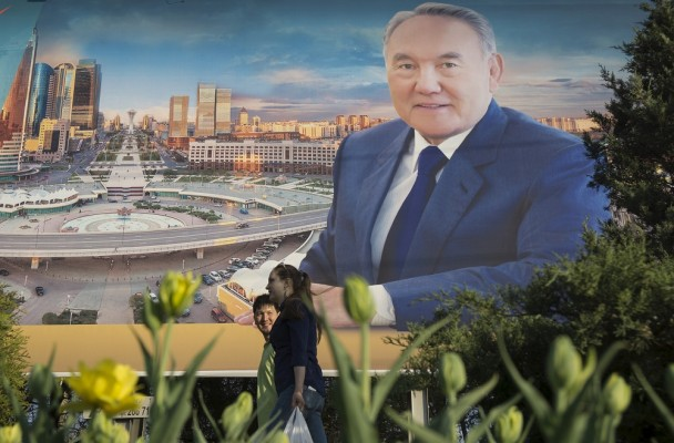 A couple walks past an election banner of Kazakhstan's President and presidential candidate Nursultan Nazarbayev in Almaty