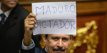"A Venezuelan opposition deputy holds up a sing reading "" Maduro dictator"" during an extraoridinary session of the National Assembly, in Caracas on October 23, 2016. Venezuela's opposition-majority legislature declared Sunday that President Nicolas Maduro's ""regime"" committed a coup d'etat when authorities blocked a referendum on removing the unpopular leftist leader from power. / AFP / FEDERICO PARRA (Photo credit should read FEDERICO PARRA/AFP/Getty Images)"
