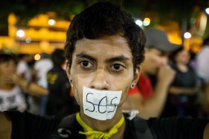 epaselect epa05936379 A woman covers her mouth with a sign reading 'S.O.S.' (the international Morse code distress signal) during vigil in Caracas, Venezuela, 29 April 2017. Venezuelan students held a 12-hour vigil in honor of people whom lost their lives during the recent anti-government rallies, while opposition parties called for another march on Monday in order to call for general elections and a new Supreme Court. EPA/MIGUEL GUTIERREZ