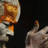 A Hindu holy man smears his body with ash and vermillion powder at the courtyard of the Pashupatinath Temple in Katmandu, Nepal, Wednesday, Feb. 15, 2012. Hindu holy men from Nepal and India have started arriving at the temple ahead of the Shivaratri festival dedicated to the worship of Lord Shiva which falls on Feb. 20. (AP Photo/ Niranjan Shrestha)